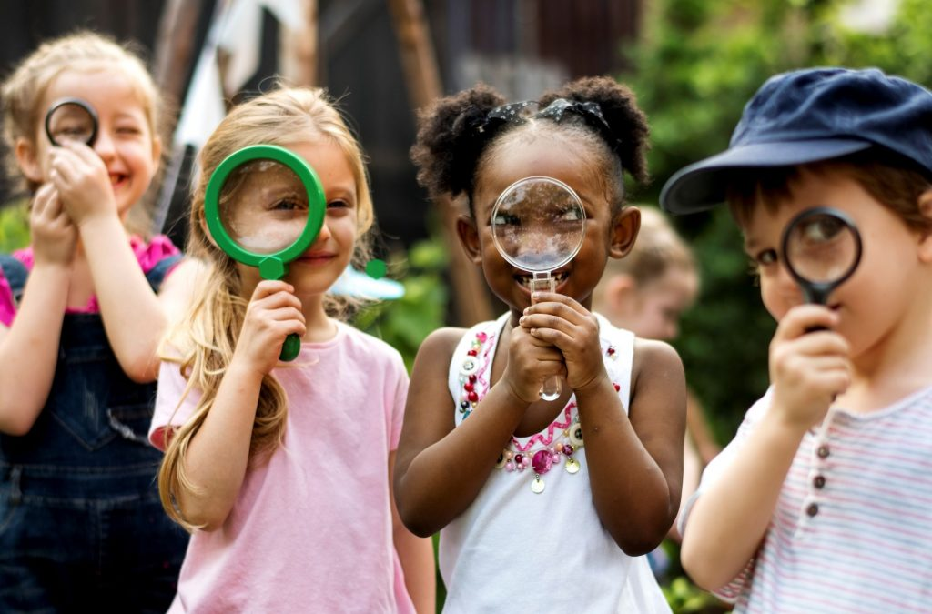 Kids exploring nature with hand lenses